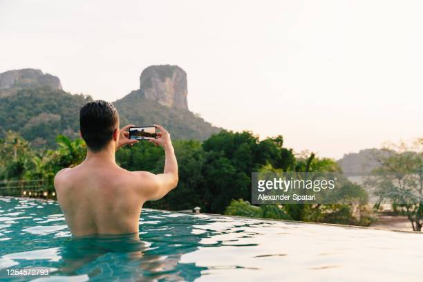 man taking pictures of mountains with smartphone from the swimming pool, thailand - モバイル撮影 ストックフォトと画像
