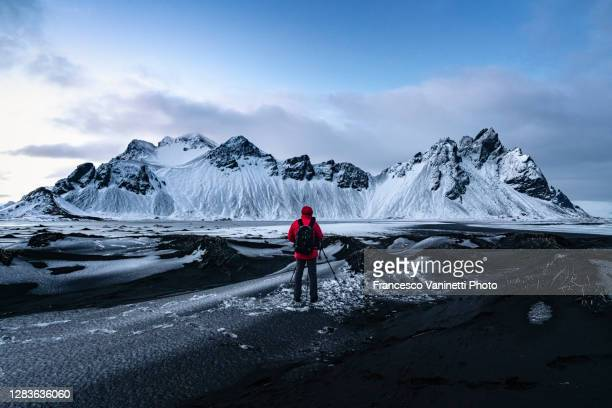 man taking pictures of vestrahorn mountain, stokksness peninsula, iceland. - black sand stock pictures, royalty-free photos & images
