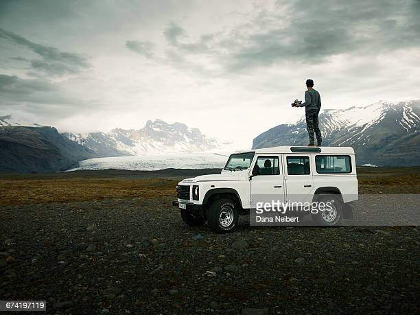 man taking pictures on top an off-road vehicle. - 4x4 stock pictures, royalty-free photos & images