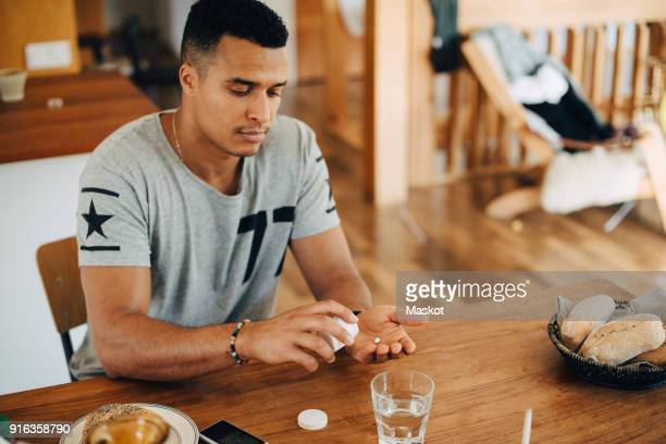 man taking pills while having breakfast at table - taking a pill stock pictures, royalty-free photos & images