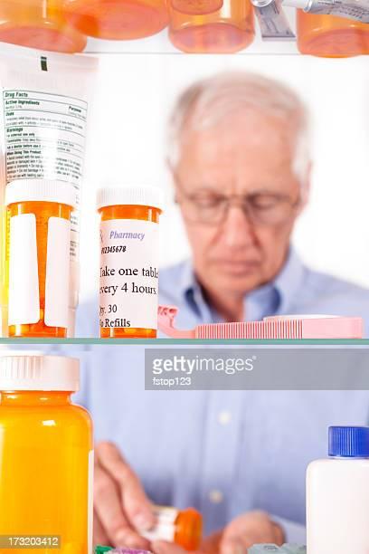 Man taking prescription pills out of medicine cabinet. Healthcare.