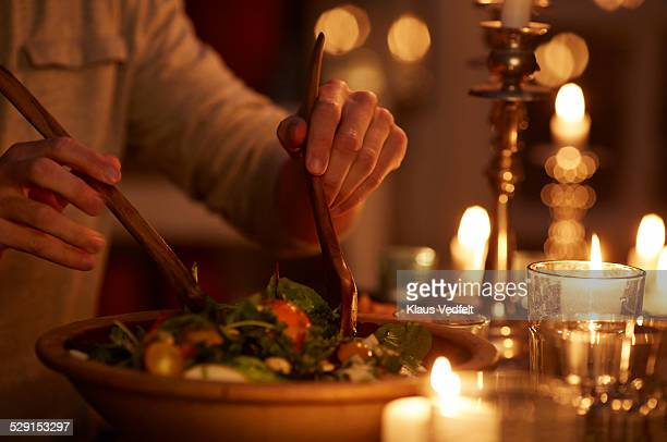 Man taking salad from bowl at candlelight dinner