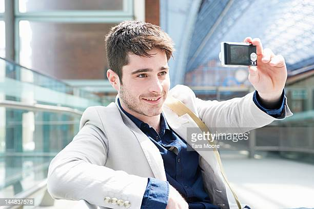 man taking self portrait with camera at station