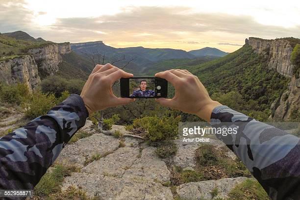 man taking selfie alone on stunning landscape. - video call stock-fotos und bilder