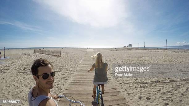Man taking selfie cycling on Venice Beach boardwalk, California, USA