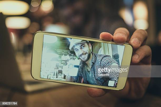 Man taking selfie in cafe
