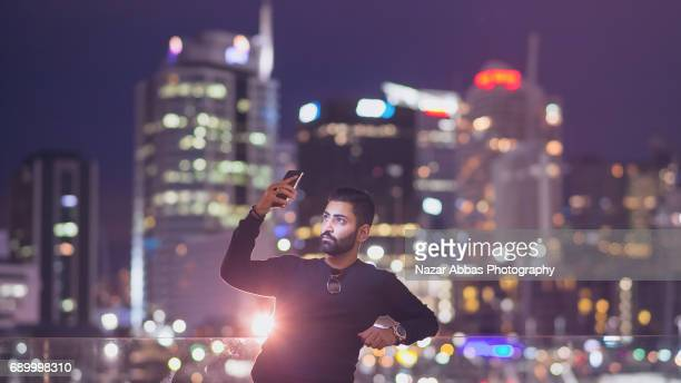 man taking selfie in city with city lights in background. - handsome pakistani men fotografías e imágenes de stock