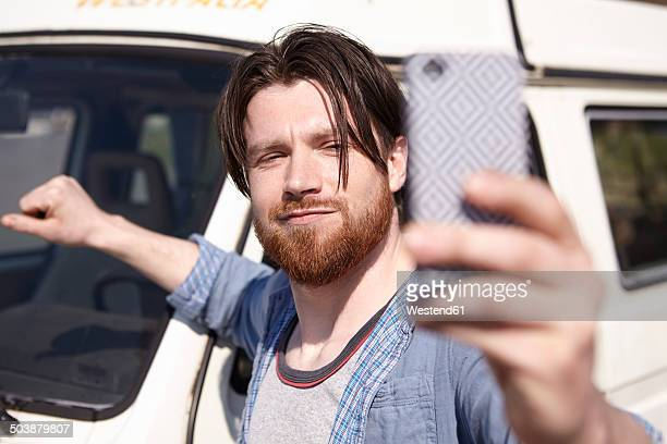 man taking selfie in front of car - showing off stock pictures, royalty-free photos & images