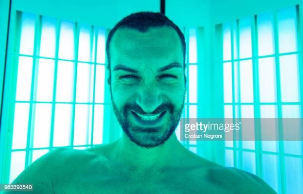 man taking selfie in the solarium with stupid expression - cristian neri foto e immagini stock