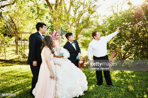 Man taking selfie of family standing with young woman in quinceanera gown in backyard