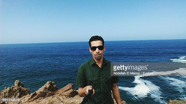 Man Taking Selfie While Standing On Rock Against Sea