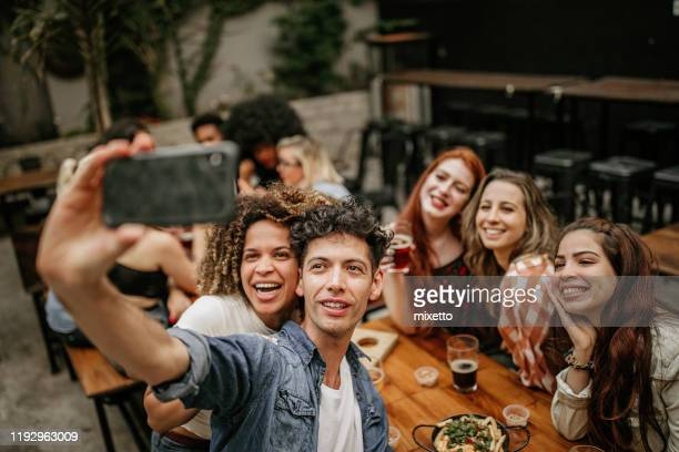 man taking selfie with friends at beer house - 20 29 years stock pictures, royalty-free photos & images