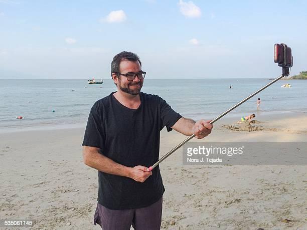 Man taking selfie with selfie stick on beach Koh Samui Thailand