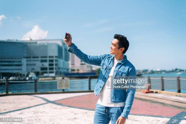 man taking selfie with smart phone - denim jacket stock pictures, royalty-free photos & images