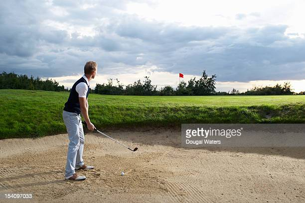 Man taking shot from bunker on golf course.