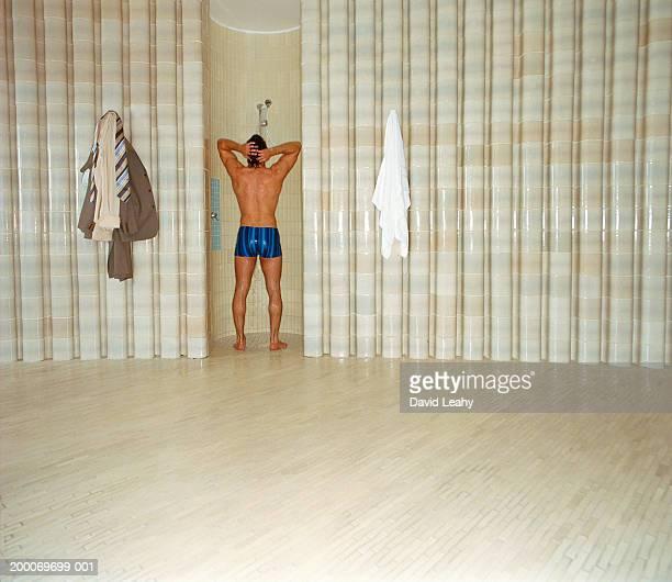 man taking shower, rear view - maenner duschen stock-fotos und bilder
