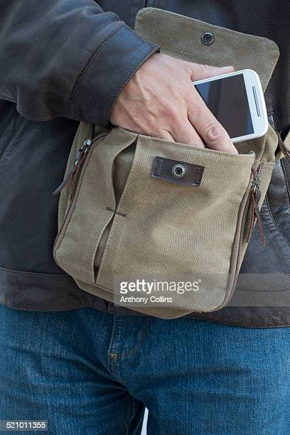 Man taking smartphone from a man bag