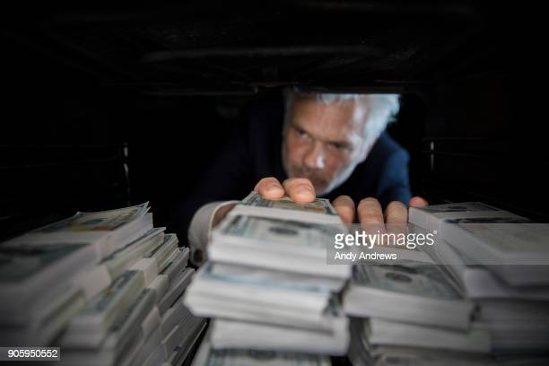 POV Man taking stacks of US dollars from a hiding place