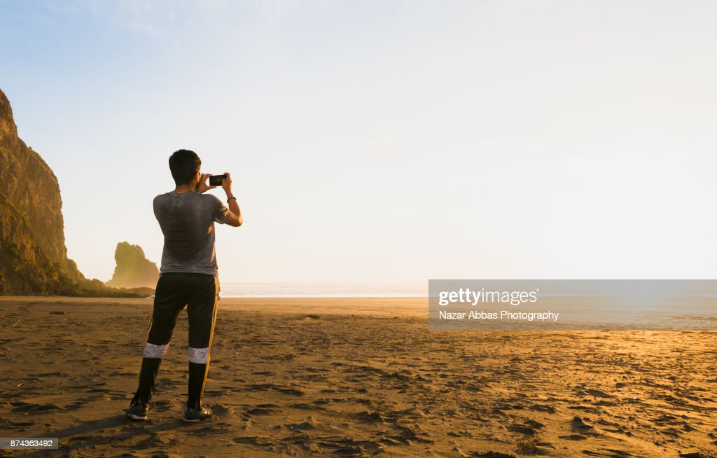 Man taking taking photo of sunset at Anawhata beach, Auckland, New Zealand. : Stock Photo