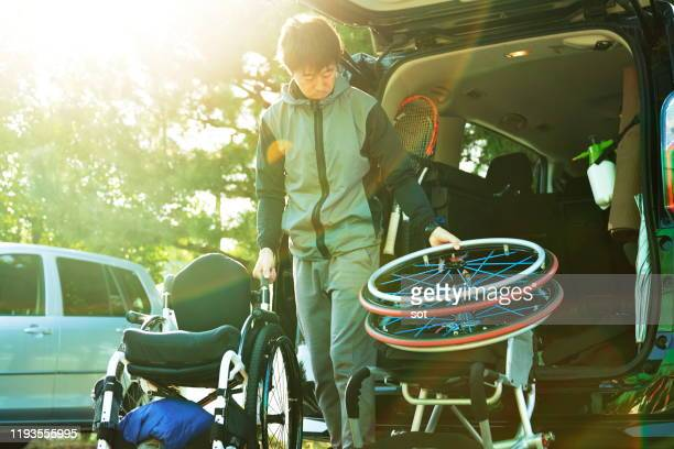 man taking tennis equipment including wheelchair out from the car - sport venue ストックフォトと画像