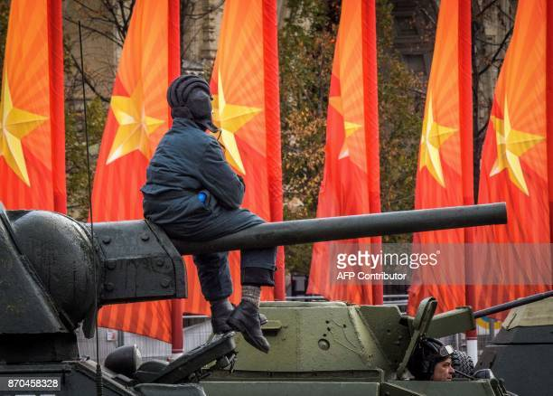 A man taking the role of a 'WWII war tank crew member' sits on its gun during a rehearsal for a forthcoming parade on Red Square in Moscow on...