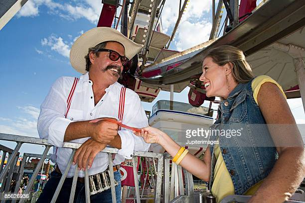 Man taking ticket from woman
