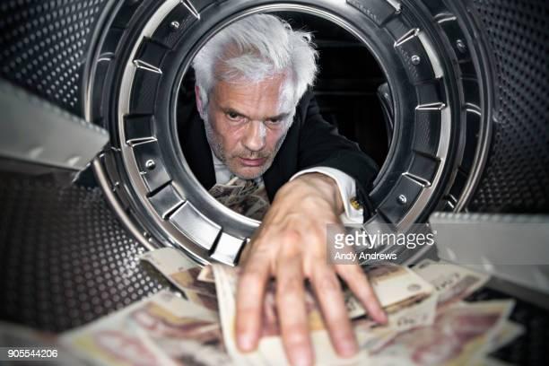POV Man taking UK pound notes out of a washing machine