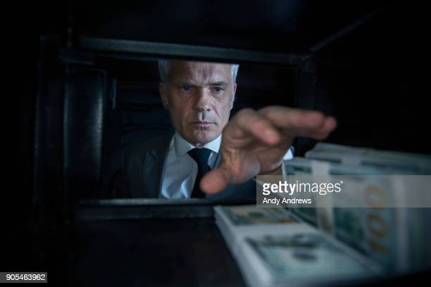 POV Man taking US dollars out of a safe