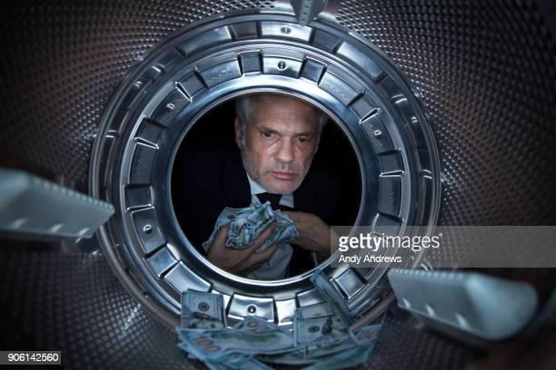 POV Man taking US dollars out of a washing machine