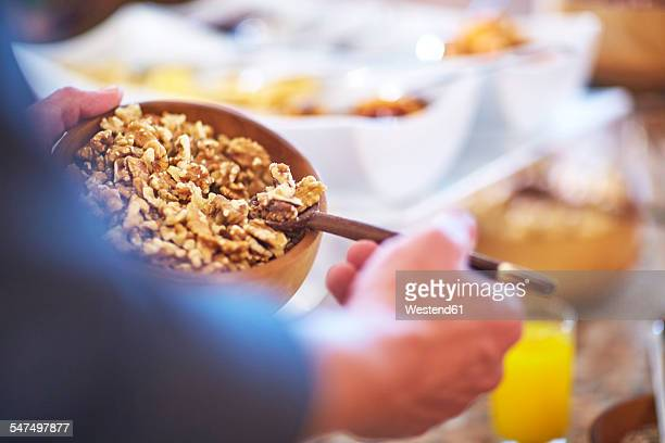 Man taking walnuts from breakfast buffet