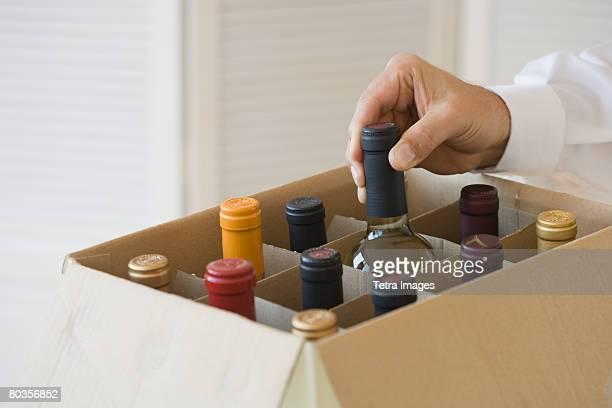 Man taking wine bottle out of case