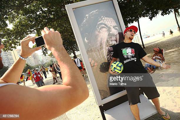 A man taks a photo next to an advertisement featuring Uruguay's Luis Suarez mocking the biting incident against opponent Giorgio Chiellini during the...