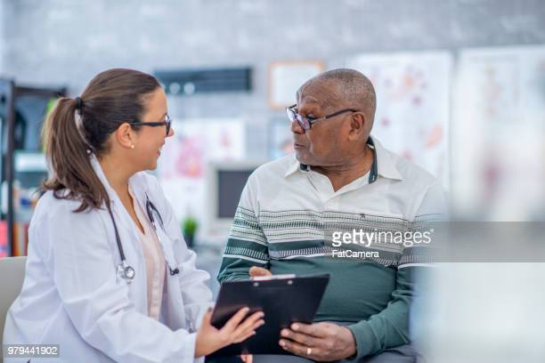 man talking advice from a doctor. - male doctor stock photos and pictures