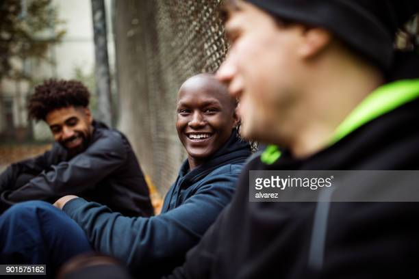 Man talking and sitting with team against fence