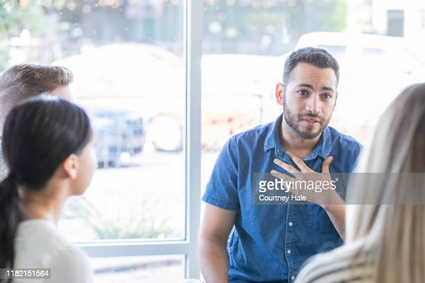 man talking during a support group meeting - post traumatic stress disorder stock pictures, royalty-free photos & images