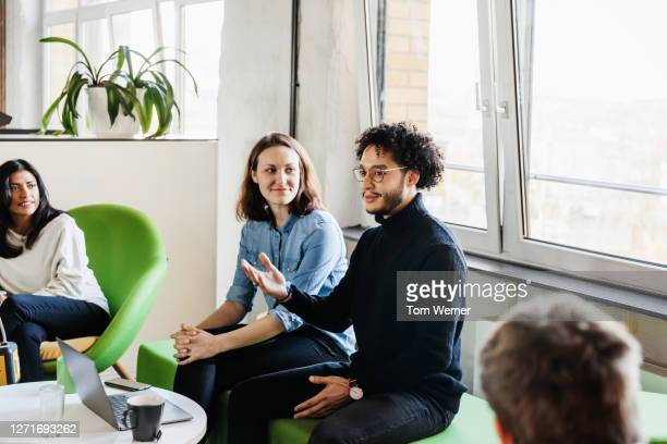 man talking during business meeting in office with colleagues - incidental people stock pictures, royalty-free photos & images