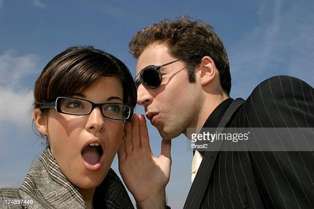 Man talking in ear of shocked woman