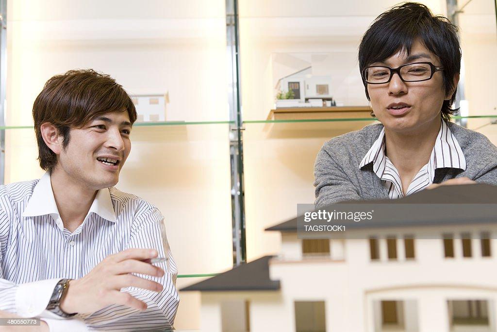 Homem a falar na frente do edifício modelo : Foto de stock