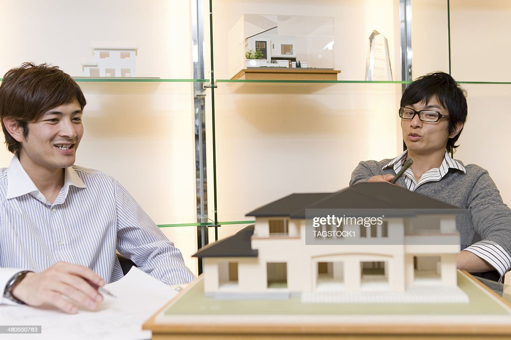 Man talking in front of building model : Stock Photo