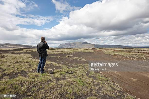 man talking in mobil phone in county field