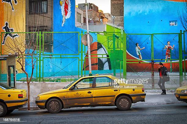 Man talking on a cell phone passes a colorful sport themed mural in central Tehran. Yellow Peugeot Pars taxis are parked at the side of the street.