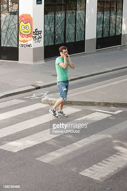 Man talking on a mobile phone on the road, Paris, Ile-de-France, France