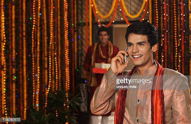 Man talking on a mobile phone with his friend holding gifts on Diwali