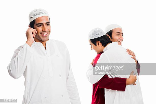 man talking on a mobile phone with his friends embracing each other during eid festival - eid al adha stock pictures, royalty-free photos & images