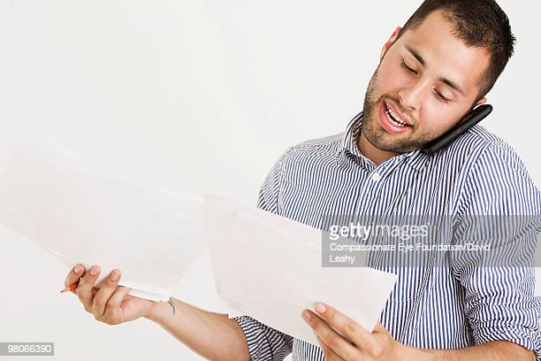 Man talking on cell phone and looking at papers