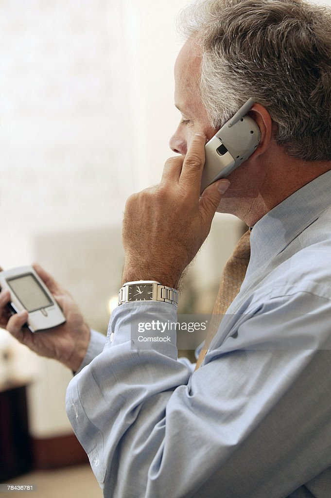 Man talking on cell phone and using PDA : Stockfoto