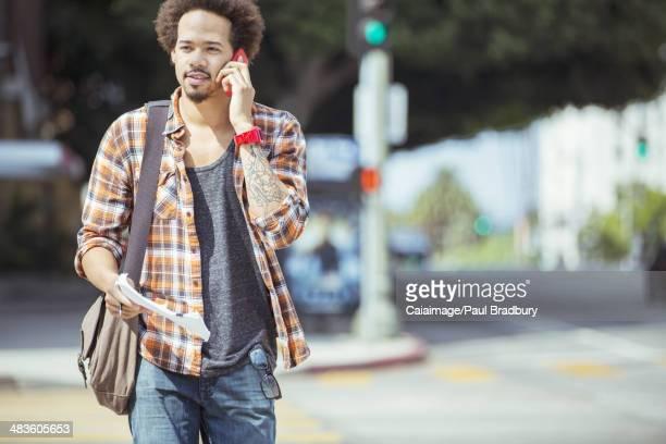 Man talking on cell phone in urban crosswalk