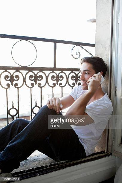 Man talking on cell phone in windowsill