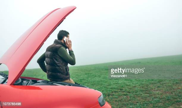 man talking on cell phone next to broken car - broken down car stock pictures, royalty-free photos & images