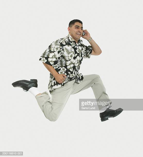 Man talking on cell phone, running in mid air